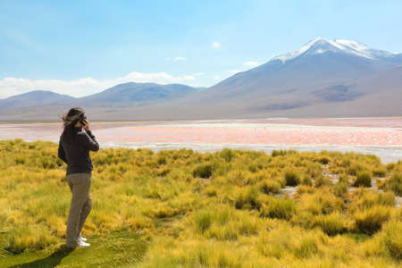 Girl speaking on the phone on the shore of Laguna Colorada, Bolivia photo