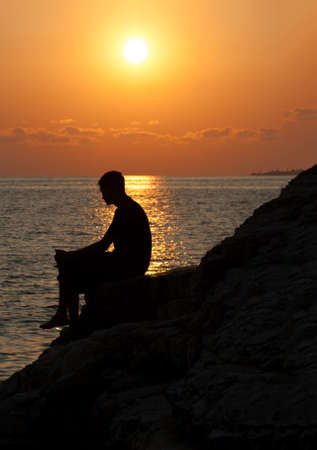 sea side: Silhouette of man from side sitting on a rock and enjoying the sunset