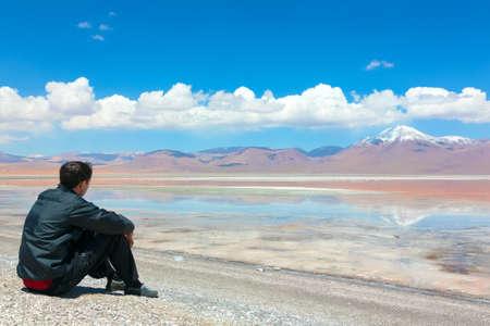 hombre solo: Hombre joven sentada sola en la orilla de la Laguna Colorada, Bolivia