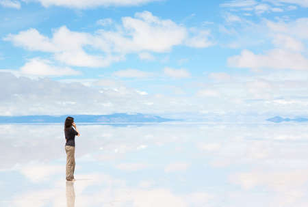 mirrored: Girl talking on the mobile phone in the middle of the lake Salar de Uyuni