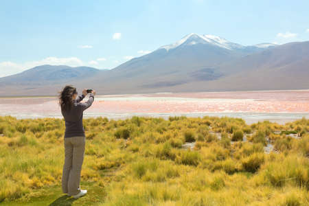 Girl taking pictures of Laguna Colorado, Bolivia photo