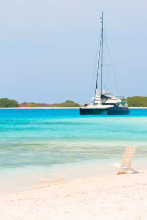 Beach chair and boat at the beach of archipelago Los Roques, Venezuela