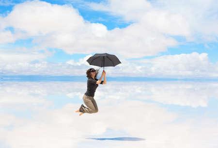 salar: Young woman jumping with umbrella Stock Photo