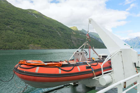 lifeboat: Lifeboat being winched from the side of a ship