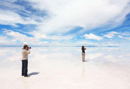 salar: Man and woman take photo of panorama lake Salar de Uyuni, Bolivia
