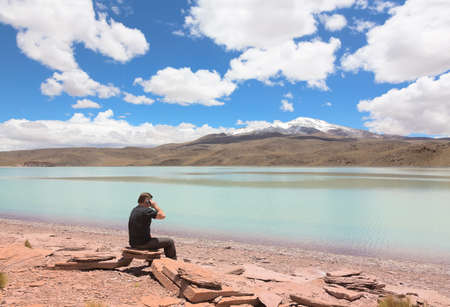 celeste: Man sitting on the shore of lagoon Celeste and talking on phone, Bolivia