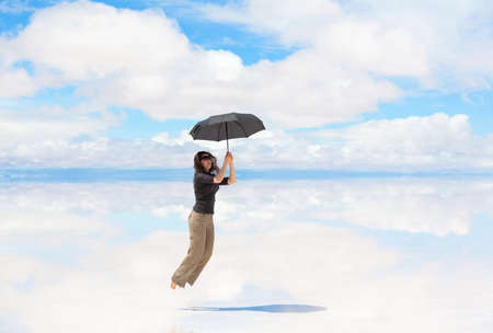 salar: Woman holding umbrella and flying on the lake Salar de Uyuni