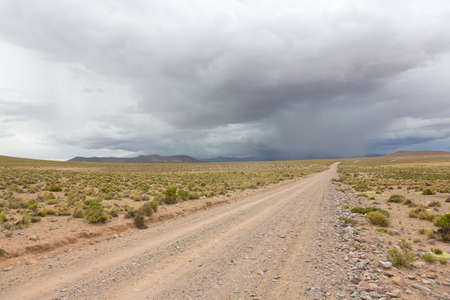 Unpaved road and storm clouds on the horizon in Bolivian altiplano photo