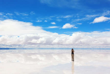 salt flat: Girl taking pictures of Salar de Uyuni, Bolivia Stock Photo