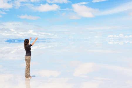 vast: Young woman standing on Salar de Uyuni with raised hands