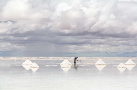 Worker performing harvesting salt on the salt lake Salar de Uyuni, Bolivia photo