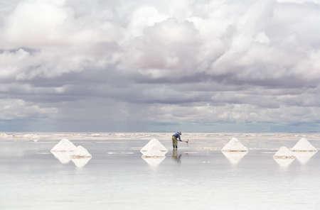 salar: Worker performing harvesting salt on the salt lake Salar de Uyuni, Bolivia