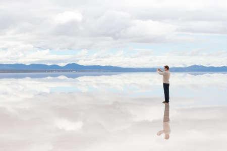 salar: Man taking pictures on camera in the middle of lake Salar de Uyuni, Bolivia