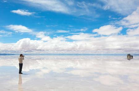salar: Man taking pictures the car on the lake Salar de Uyuni, Bolivia Stock Photo