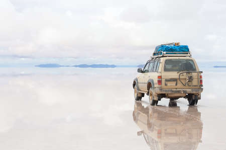 Car moving on the reflected surface of Salar de Uyuni lake in Bolivia photo