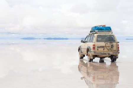 salar: Car moving on the reflected surface of Salar de Uyuni lake in Bolivia Stock Photo
