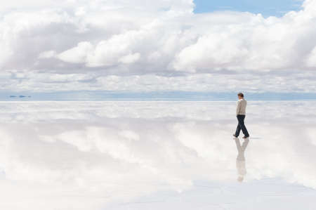 salar de uyuni: Man wolking in the middle of lake Salar de Uyuni, Bolivia Stock Photo