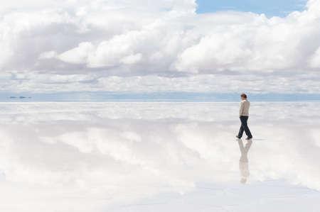 bolivia: Man wolking in the middle of lake Salar de Uyuni, Bolivia Stock Photo