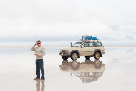 reflected: Man standing next to off-road car on reflected surface of lake Salar de Uyuni in Bolivia