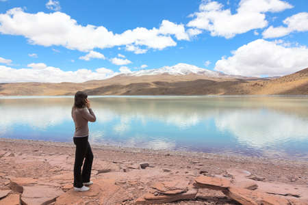 celeste: Woman talking on the mobile phone at the shore of lagoon Celeste, Bolivia