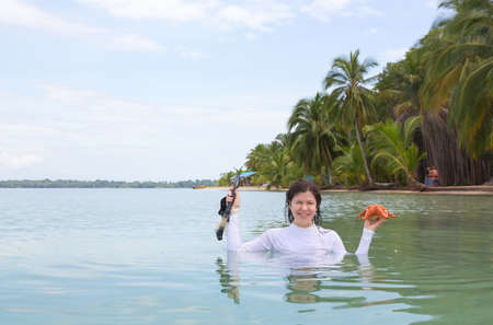 Woman with starfish and diving mask in hands, archipelago Bocas del Toro, Panama photo