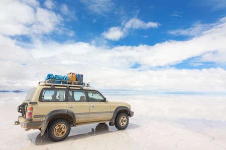 Off-road car on the reflected surface of lake Salar de Uyuni in Bolivia