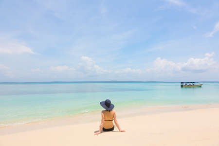 archipelago: Woman sitting on the beach, archipelago Bocas del Toro, Panama Stock Photo