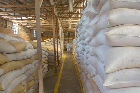 Stapel zakken met koffiebonen in het magazijn