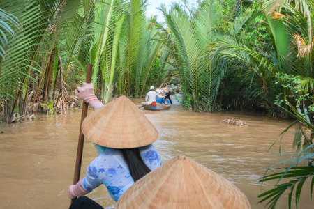 delta: Vietnamese woman paddling in the Mekong River Vietnam