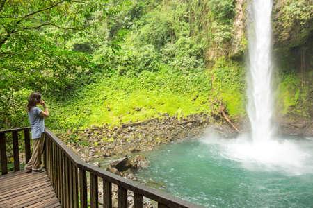 fortuna: Woman speaking on the phone at La Fortuna waterfall Costa Rica