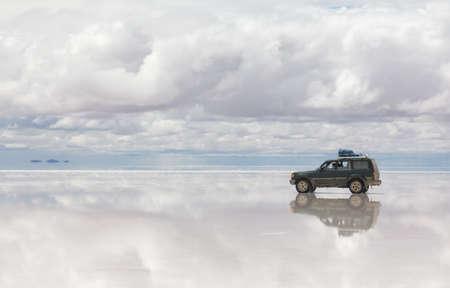 unruffled: Car on the reflected surface of Salar de Uyuni lake in Bolivia