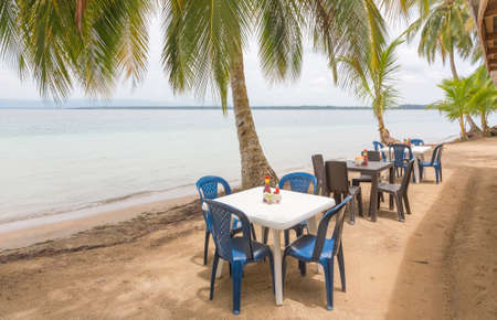 beach bar: Restaurant tables under the palm trees on the beach Stock Photo