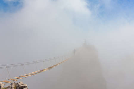 Man crossing the chasm on the hanging bridge in fog (focus on the middle of bridge) Stock Photo