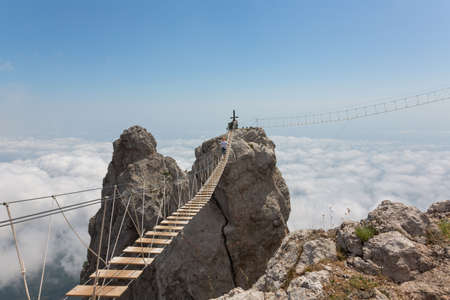 dangerous: Man crossing the chasm on the hanging bridge (focus on the middle of bridge) Stock Photo