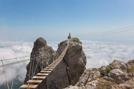 Man oversteken van de kloof op de hangbrug (gericht op het midden van de brug) Stockfoto