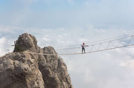 dangerous: Man crossing the chasm on the hanging bridge (focus on the man) Stock Photo