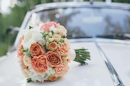 結婚式の白いレトロな車のボンネットの上の花束