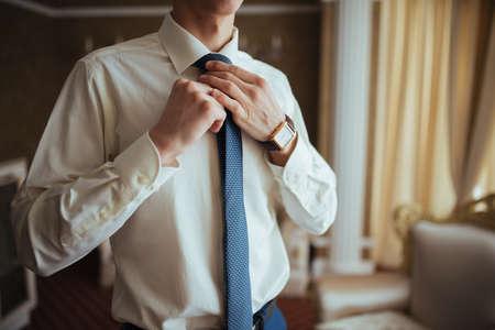 mauve: The groom adjusts his tie. Wedding preparation Stock Photo