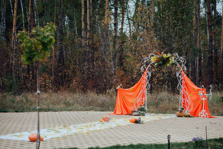 beautiful wedding arch made of cloth with autumn decorations