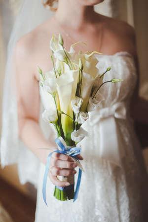 calas blancas: ramo de novia en las manos de la novia