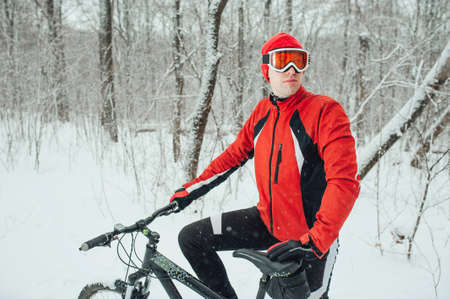 cyclist in a red outfit in the winter snowy forest