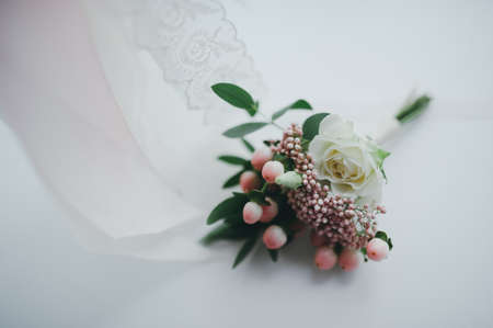 groom boutonniere on a white veil bride Stock Photo