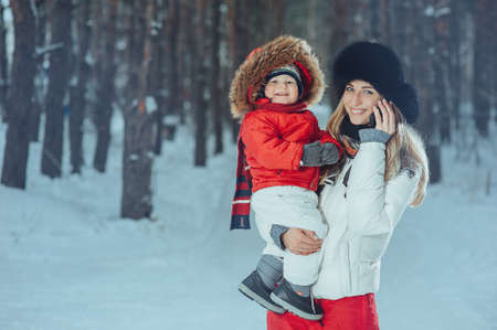 baby in mothers arms on the background of the winter forest Stock Photo