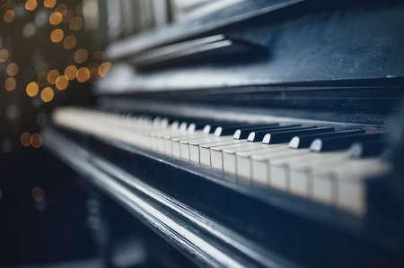 transcription: Closeup of vintage piano keyboard. Beautiful blur background