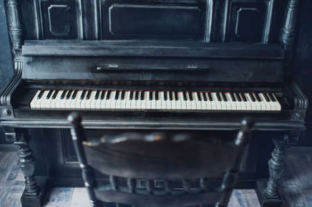 antique chair: Black antique piano and a chair. General form