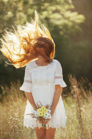 flyaway: Girl with a bouquet of wildflowers in the setting sun. flying hair Stock Photo