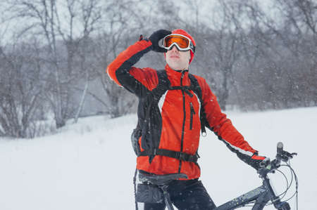 cyclist in red in the winter snowy forest