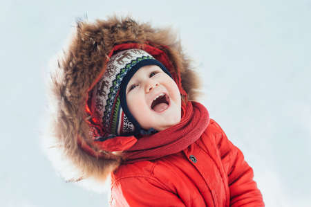child smiling on the background of the winter forest Archivio Fotografico