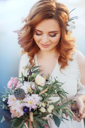 floral decoration: Beautiful bride with a bouquet of different flowers on  background  lake. Rustic Wedding