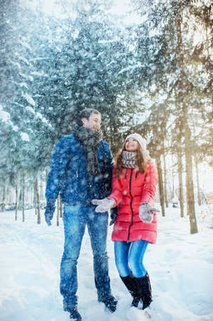stroll: Young and beautiful couple, man girl playing in a winter park with snow, throw the up. Stock Photo